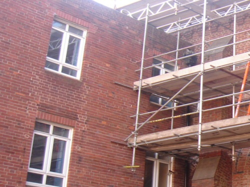 Gantry scaffolding forming a dropper or bridge over a fragile roof during renovation at St Mary's College, Blackpool